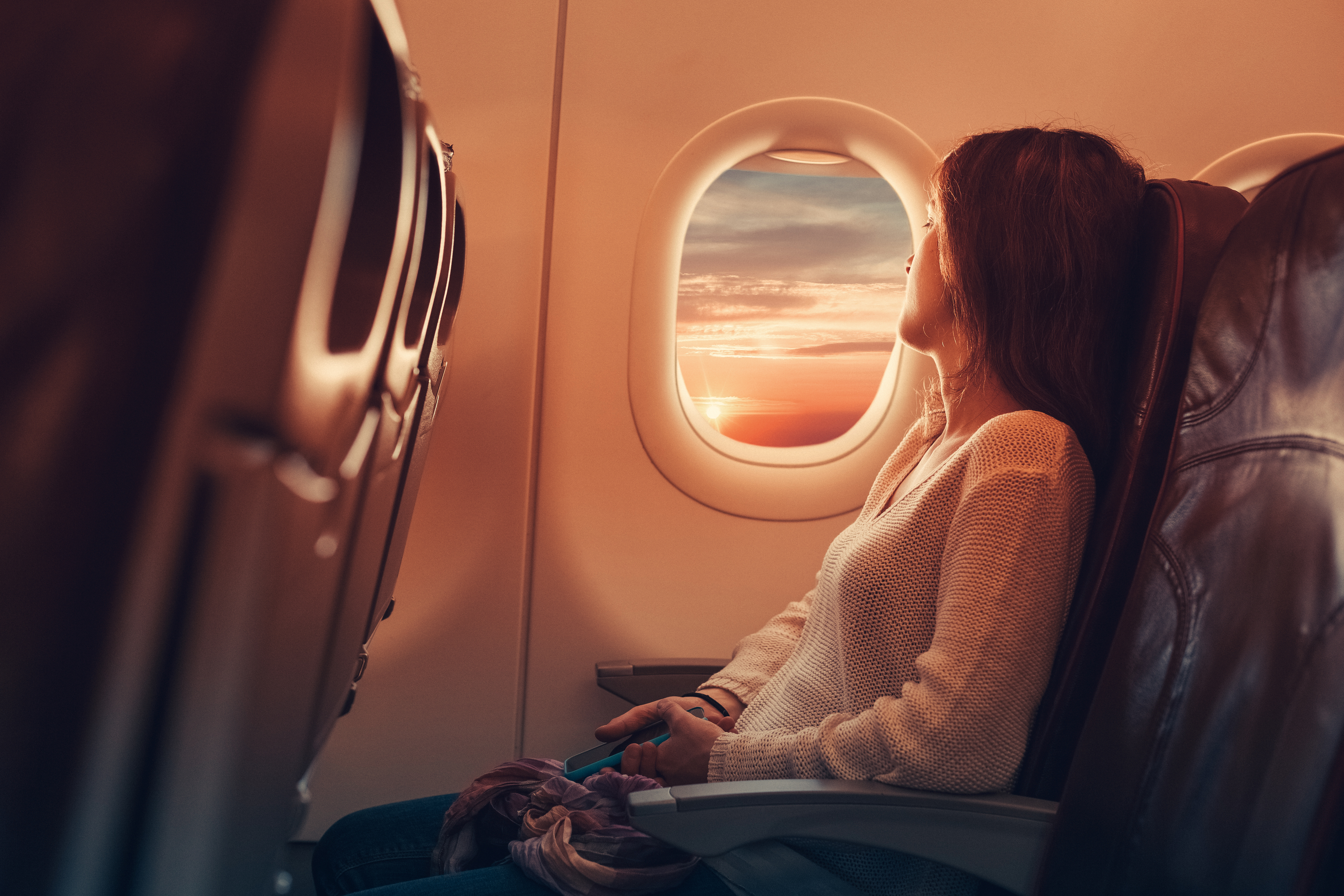 woman in window seat looking out airplane window