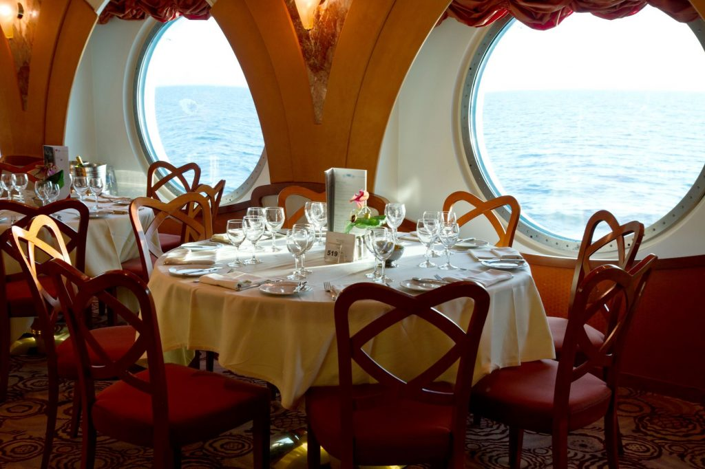 Fine dining table set onboard a cruise looking out at the ocean