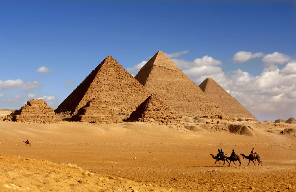 Camel back riders in front of pyramids in Cairo Egypt